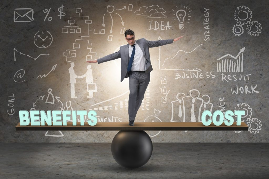 Businessman balancing between cost and benefit i